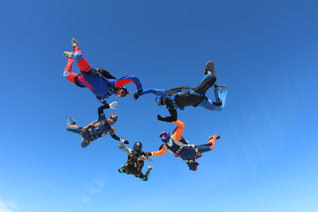 A group of skydivers are flying in the blue sky.