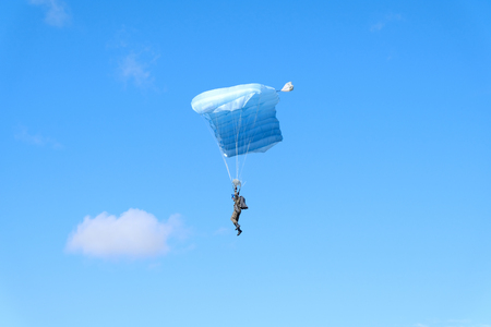 Blue canopy with military skydiver is in the sky. Standard-Bild