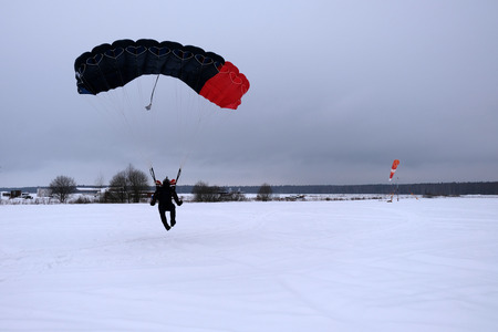 Skydiver is landing on the snowy field. Banco de Imagens