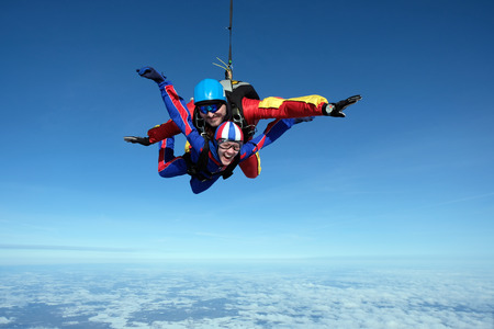 Skydiving. Man and woman are flying in the sky together. 스톡 콘텐츠