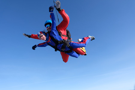 Tandem skydiving. Big man and a little woman are flying together. 写真素材