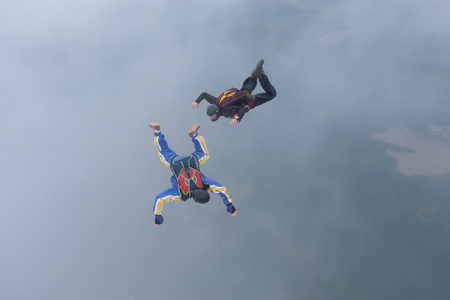 Two skydivers are training in the sky.