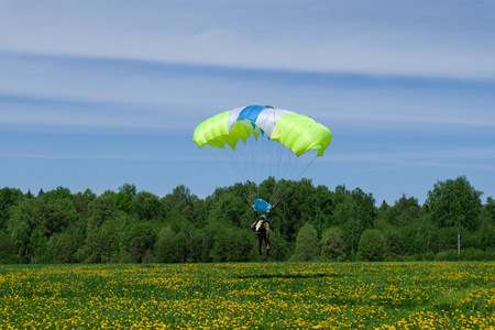 An yellow parachute is landing on the dandelion field. Stock Photo