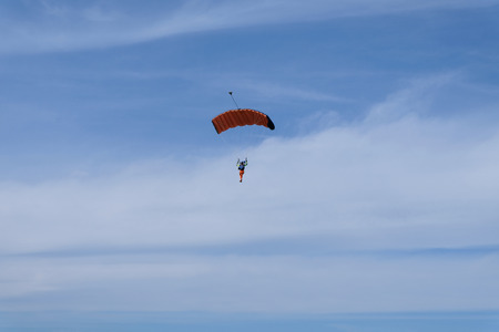 A red parachute is in the blue sky.
