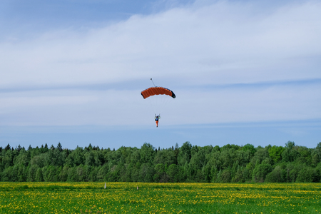 Parachute is landing on the dandelion field. Stock Photo