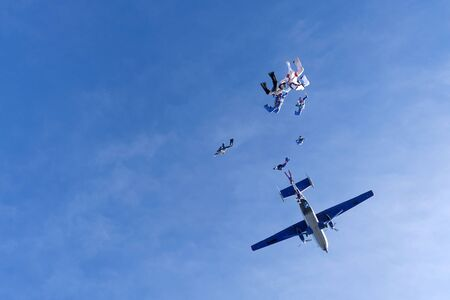 Skydivers are in the blue sky.
