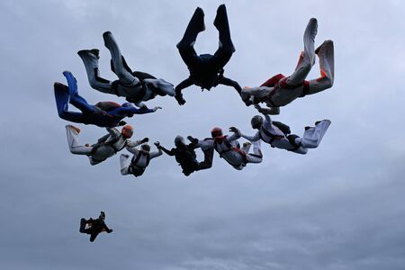Formation skydiving in the cloudy sky. 版權商用圖片