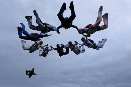 Paracadutismo in formazione nel cielo nuvoloso.