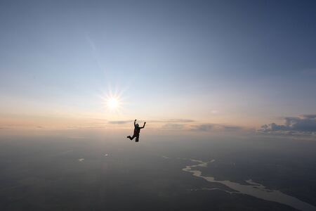 Skydiver is falling in the sunset sky.