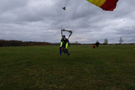 Tandem skydiving. Landing on the field.
