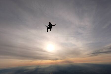 Skydiving. A skydiver is sitting in the sunset sky. 版權商用圖片