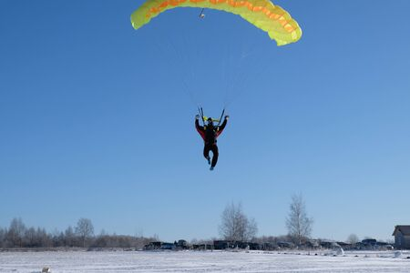 Skydiver is landing on the snowy field. Stock fotó
