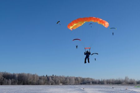 Skydiving. AKydiver lands on the snowy field. Stock fotó