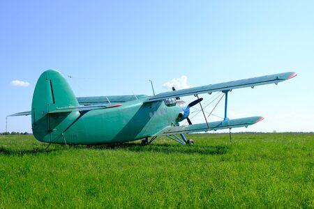 An small biplane is at an aerodrome.