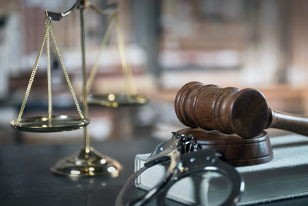 Law concept - Open law book with a wooden judges gavel on a courtroom or law office