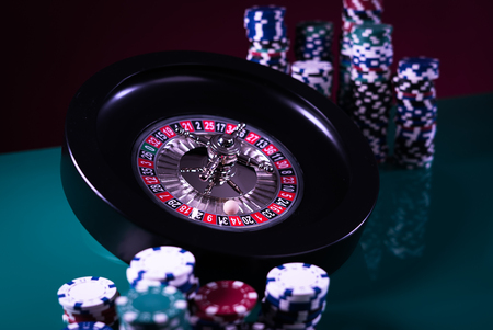 Casino theme. High contrast image of casino roulette, poker game, dice game, poker chips