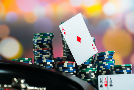 Casino theme. High contrast image of casino roulette, poker game, dice game, poker chips on a gaming table