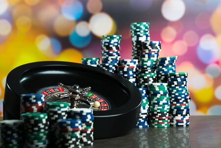 High contrast image of casino roulette, poker game, dice game, poker chips on a gaming table, all on colorful bokeh background.