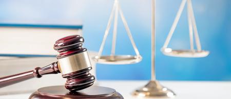 Concepto de ley, justicia y sistema legal con un símbolo de juez de martillo de madera sobre fondo azul. Foto de archivo