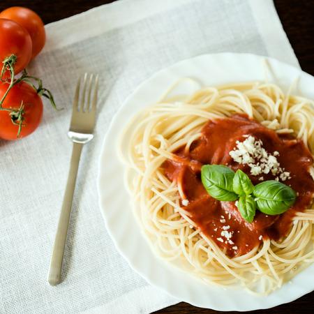 Italian pasta spaghetti topped with a tomato Stock Photo