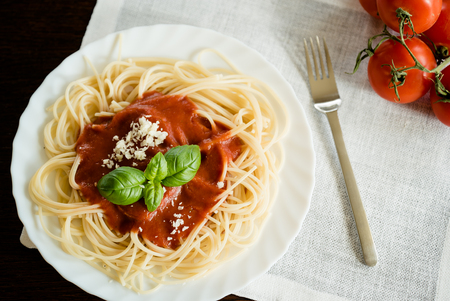 Italian spaghetti pasta topped with a tomato and fresh basil