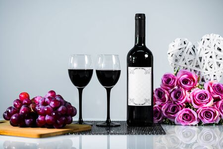 Red wine with grapes and flowers on white