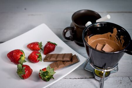 Chocolate fondue with fresh berries on wooden table 스톡 콘텐츠
