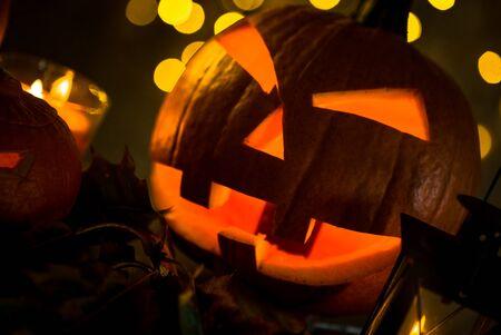 Halloween pumpkin head jack lantern with burning candles in scary deep night