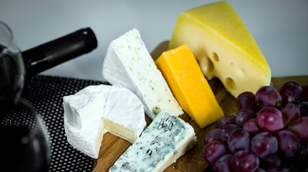 Different types of cheese with grapes Фото со стока