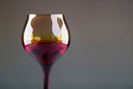 Pouring red wine from a bottle into a wineglass: wine tasting and celebration