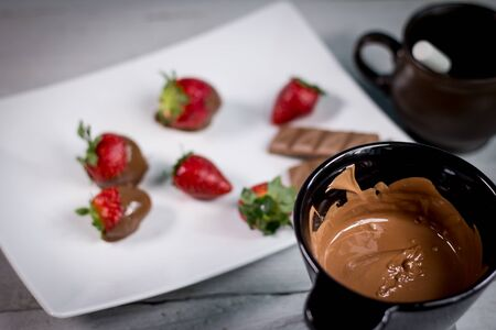 Chocolate fondue melted with fresh strawberries and milk chocolate