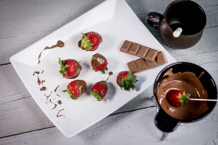 Dipping fresh fruits into pot with tasty chocolate fondue