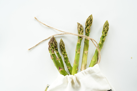 Bundle of fresh green asparagus on a white table with copy space.