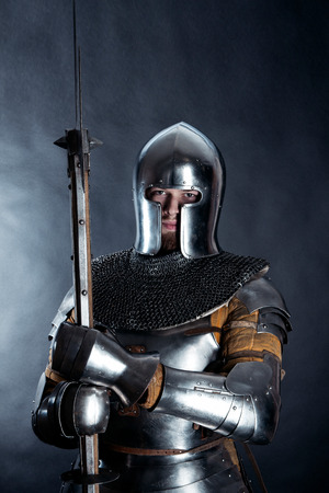A medieval warrior in a helmet and with a halberd. Knight on dark background Stock Photo