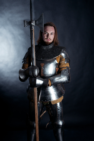 A medieval warrior and with a halberd. Knight on dark background Stock Photo