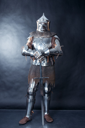 A medieval warrior with a sword. Knight on dark background