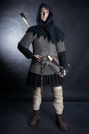Medieval archer armed with a bow and arrows. Knight on dark background Stock Photo - 78458889
