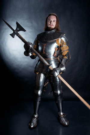 A medieval warrior with a halberd. Knight on dark background