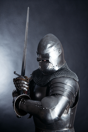 A medieval warrior with a sword and in a helmet. Knight on dark background Stock Photo