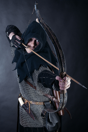 Medieval archer armed with a bow and arrows. Knight on dark background