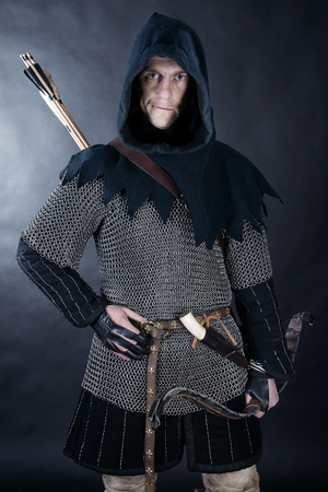 Medieval archer armed with a bow and arrows. Knight on dark background Stock Photo - 78458894