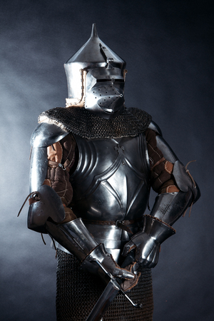 A medieval warrior in a helmet with a sword. Knight on dark background Stock Photo