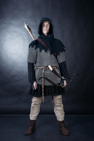 Medieval archer armed with a bow and arrows. Knight on dark background Stock Photo - 78458898