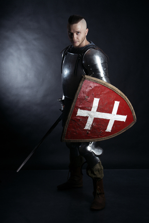 A medieval warrior with a sword and a shield. Knight on dark background
