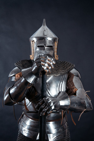 iron man: A medieval warrior in helmet with a sword. Knight on dark background