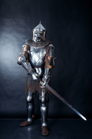 A medieval warrior in helmet with a sword. Knight on dark background
