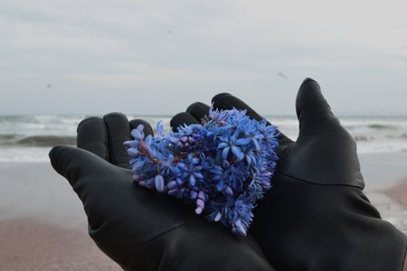 a female hand holds a lilac against the background of the sea, waves with wind Odessa, Ukraine Imagens