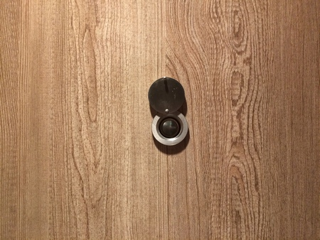 Lens peephole on new light wooden door