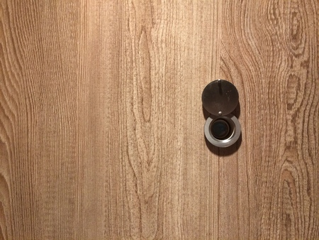 Lens peephole on new light wooden door
