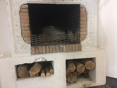 wood fired stove with fire-wood, fire-irons, and briquettes from bark.